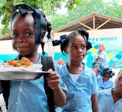 Children receive school lunch as part of the World Food Programme's efforts to encourage school attendance and nutrition among children. [Photo: WFP]