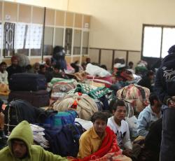 Bangladeshi men, some of whom have been awaiting onward transport for almost two weeks, take shelter in one of the few covered spaces at the Saloum Land Port on the Egyptian/Libyan border. Credit: OCHA/David Ohana
