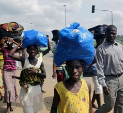 Residents of the Abobo suburb carry their belongings as they flee the intense fighting, Credit: UNHCR/H.Caux