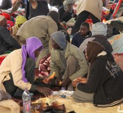 Chadian men who have fled the unrest in Libya share a meal under the limited shelter at a waiting area at the Saloum Land Port on the Egyptian/Libyan border. Credit: OCHA/David Ohana