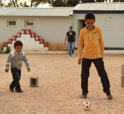 Displaced children from Ajdabiya play football inside the former construction camp where they are housed in Benghazi. Credit: IRIN/Kate Thomas