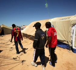 Three Ethiopian friends who survived more than two weeks adrift in the Mediterranean wander through Choucha Camp. Credit: UNHCR/H.Caux