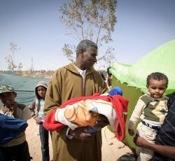 "In Libya, Mohamed Othman holds his two-day-old daughter, Entisah. Her name means ""Victory"" in Arabic. Entisah was born in this make-shift, tented camp, around 25km from Ajdabiya. The camp houses many families from the thousands that fled Ajdabiya along the desert highway as fighting escalated in the town during Libya's armed uprising. With no access to the hospital, the birth was traditional. Credit: UNHCR/Phil Moore"