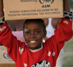 A young girl carries her box from a United Nations food distribution. Credit: UN/MINUSTAH/Logan Abassi