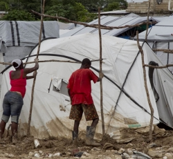 Residents of a Port-au-Prince IDP camp cleaning up after heavy rains and flooding swept the area. Credit:MINUSTAH