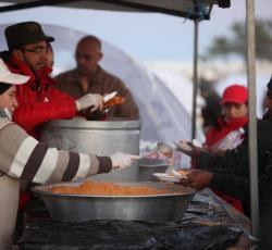 IFRC and other partners serve food to thousands of people each day at a transit camp near the Tunisia-Libya border. Credit: OCHA/David Ohana