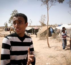 "In Libya, 19-year-old Khalid, a student from Ajdabiya, has been forced to leave his home due to shelling and fighting in the town. He and his family have been living in tents in the arid scrubland lining the Tobruk-Ajdabia highway. Hundreds of people line up the desert road. Khalid explained: ""We all need water, tents and food. It's very cold here at night."" Credit: UNHCR/Phil Moore"