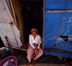 A local resident awaits for relief aid infront of her make-shift house in Datu Piang, Maguindanao. Credit: IRIN/Veejay Villafranca