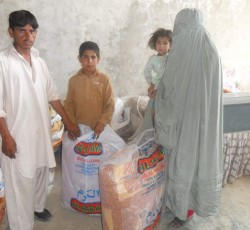 Basmina Jan and her children collect the winter package at KADO's NFI distribution point in New Sabzi Mandi of District Kohat. Credit: KADO/Sumaya Shafi