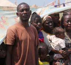 16 Jan 2014, Bangui, CAR: Robert Demba stands with his family in front of their shelter at the international airport in Bangui. They have been living there since fighting started in 5 December. Across the Central African Republic, more than 800,000 have been forced from their homes. Credit: OCHA/C. Illemassene