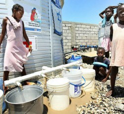 The French Red Cross provides water, sanitation and toilets for 11,000 IDPs at the Centre d'Hebergement Provisoire Automica Dahaitsu in Port-au-Prince. Water buckets are lined up early in the morning as children wait until the water is distributed at noon everyday by community leaders in the camp. Credit: MINUSTAH