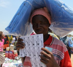 September 2013. Katanga, DRC: Safi Mutombo displays her page of coupons. They are worth about US$90. In 2012, the CHF-funded organizations organized 23 fairs, where displaced families received a collective $16.3 million in support. Credit: OCHA/Gemma Cortes