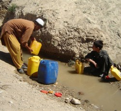 Hafiz Jan and his son collect water from a filthy canal in Chaghcharan, capital of Ghor Province, western Afghanistan. Credit: IRIN/Mohammad Popal