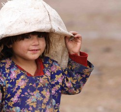 A little girl plays with her WFP food collection bag in Jalozai camp, northern Pakistan. Credit: OCHA/Stacey Winston