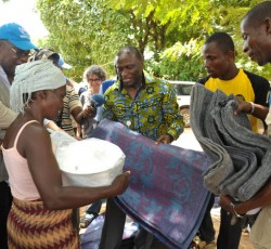 Ndolamb Ngokwey handing out a blanket and mat to a woman in Guiglo Internally Displaced Persons (IDP) camp, June 2011. Credit: OCHA