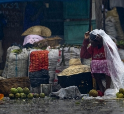 A vendor struggles to ply her wares in heavy rains. Credit: UNMINUSTAH/Logan Abassi