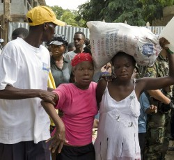 18 July 2008: Residents carry away their food supplies from a distribution centre supervised by the members of the Brazilian battalion of the United Nations Stabilization Mission in Haiti (MINUSTAH). The government of Mexico has donated 20 tonnes of food supplies for distribution throughout the country. Credit: Jean Rabel