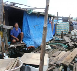 4 Feb 2014, Guiuan, the Philippines: Moreto Buenaflor and his family have tried to repair their home with scraps of destroyed buildings and emergency plastic sheets. Their shelter is flimsy and extremely vulnerable to storms and floods. Credit: OCHA/Gemma Cortes
