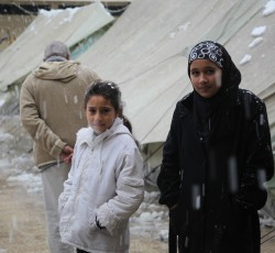 Dec 2014, Damascus, Syria: Two girls brave the bitter cold of the Damascus winter in the Jaramana Temporary Collective Shelter. Despite repeated calls from the international community, and despite three resolutions from the Security Council, the conflict in Syria continues to exact a heavy toll on civilians. Credit: UNRWA/Taghrid Mohammad.