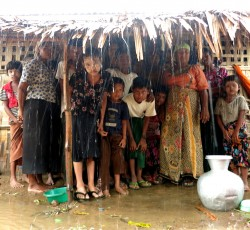 Families take shelter from the monsoon rains under the awning of a long house shelter in Myanmar's Rakhine State. Aid agencies are concerned about the potential impact of a cyclone or tropical storm on vulnerable communities. Credit: OCHA