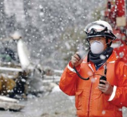 A rescue worker uses a two-way radio transceiver during heavy snowfall at a factory area devastated by an earthquake and tsunami in Sendai, northern Japan, 16 March 2011. Credit: REUTERS/KIM KYUNG-HOON, courtesy The Thomson REUTERS Foundation - ALERTNET