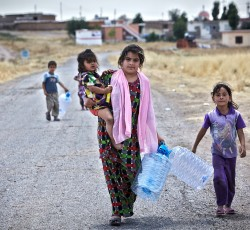 June 2014, Anbar, Iraw: An Iraqi woman from Mosul holds her daughter in one hand and empty water containers in the other. Two other children follow her in search of water near the Garmava temporary camp in central Iraq. Credit: UNHCR/S. Baldwin