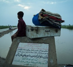 9 September 2011, Sindh Province, Pakistan: A boy displaced by flooding sits with his belongings in hope of returning home. Credit: IOM Pakistan
