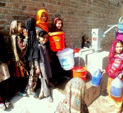 Children in Bara using a newly installed hand-pump to draw water from the well. Credit: IRC