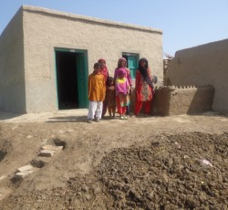 2014, Punjab, Pakistan: Asho Mai and some of her children stand proudly in front of their new home. The small shelter was built by an NGO with funding from the OCHA-managed Emergency Response Fund. Credit: CESVI