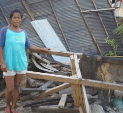 Rebecca Piñar (38) is standing in front of her shattered house. Although Typhoon Haiyan destroyed her home, she does not want to move farther inland as this would mean leaving her relatives, animals and corn fields behind. Credit: OCHA/Jennifer Bose