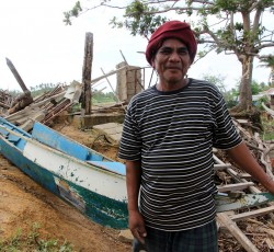 24 Jan 2014, Concepcion, the Philippines: Danielo Delosindo, a father of five, poses in front of his destroyed boat. His fishing business used to be the sole source of income for his entire family. Credit: OCHA/Gemma Cortes