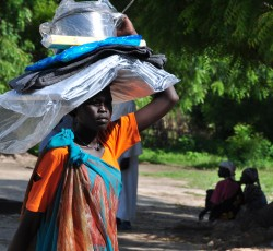 June 2014, Unity State, South Sudan: A woman carries relief supplies from a distribution site in Leer County, Unity State. Leer is hosting over 40,000 internally displaced people mainly from neighbouring Jonglei State. Credit: OCHA/ Guillaume Schneiter