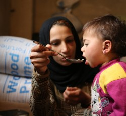 3 December 2013, Adra, Syria: Fatema, 24 years old - displaced with her family from Douma in rural Damascus to Adra - feeding her 18 month old daughter Haneen lunch. Credit: WFP/Abeer Etefa