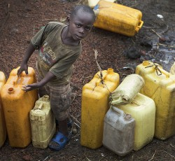August 2012, DRC: A young displaced boy waits at water point in Kanyaruchinya IDP camp in the outskirts of Goma. Credit: MONUSCO/Sylvain Liechti
