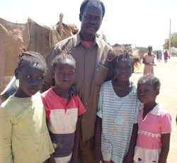Man and children at the Shegara departure point in Khartoum, awaiting transport to South Sudan.
