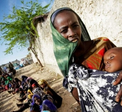 A Somali woman holds her severely malnourished baby outside a tent serving as a medical clinic established by the African Union Mission in Somalia. Credit: AU-UN IST/Stuart Price