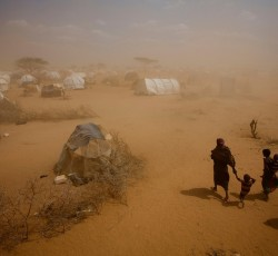 9 July 2011: Somali woman and children walk through a dust storm to their tent in Dagahaley refugee camp, north-eastern Kenya. Land degradation and water shortages are putting growing pressure on relief operations. CREDIT: UNICEF/ Kate Holt