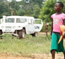 In Bahé Village, a girl walks past United Nations peacekeepers patrolling the area after armed men reportedly threatened civilians. UNICEF/Asselin.