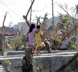 10 November, Philippines: Two children walk past downed trees and other destruction caused by Super Typhoon Haiyan in Tacloban City one of the areas worst affected by the disaster. Credit: UNICEF
