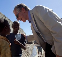 Haiti: Humanitarian Coordinator Nigel Fisher talks to children while touring a newly constructed canal in the Zidor neighborhood of Cap Haitian. Credit: MINUSTAH/ Victoria Hazou