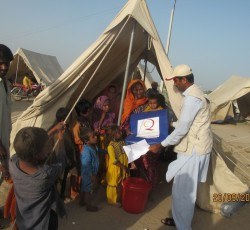 Aid worker delivers relief supplies to families displaced by floods. Credit: OCHA