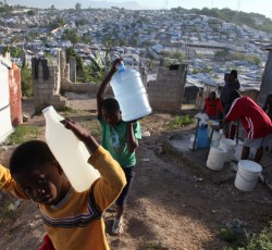 December 2010, Haiti: Children carry jugs of water at a camp for earthquake victims, in the Delmas District of Port-au-Prince, the capital. Near them, people collect water from a spigot. Credit: UNICEF