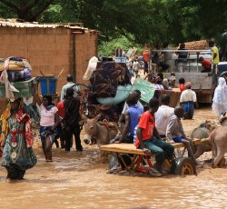 Carrying personal belonging away from flooded areas in Niamey anyway they can. Credit: OCHA/Franck Kuwonu