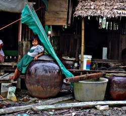 A child leans on a water jar outside demolished houses. Villagers start on reconstructing the damages caused by the cyclone in Hnarkaung Chaung town in Kum Yangon town in the Irrawady delta region. Credit: IRIN/VJ Villafranca