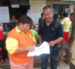 December 2012: A local NGO worker hands over a list of available aid supplies to a Government disaster coordinator in Davao, Mindanao. Credit: OCHA/Imogen Wall