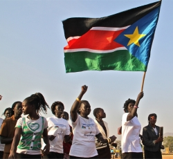 Women carry a flag in southern Sudan. Credit: IRIN/Jose Miguel Calatayud