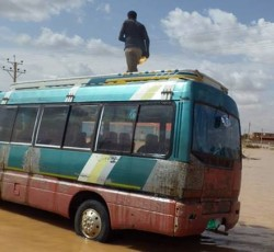 August 2013, Khartoum, Sudan: A man stands on a bus in the Sharg al Nil Area of Khartoum.  Flooding across Sudan may have affected as many as 530,000 people since the start of August. Credit: OCHA/Rodraksa