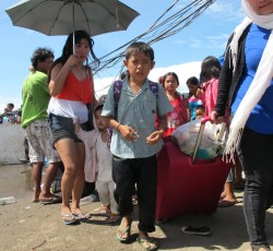 21 November 2013, Tacloban, Philippines: A child and his family at the airport in Tacloban. All families are processed by the Department of Social Welfare and Development (DSWD). Credit: OCHA/M. Cochrane