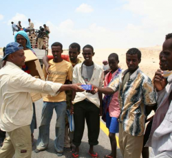 Aid workers from a Yemeni NGO distribute food to newly arriving Somali and Ethiopian migrants. Credit: UNHCR/J.Björgvinsson